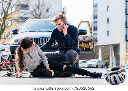 Full length view of a worried young driver calling the ambulance after hitting and injuring accidentally a female bicyclist on a city street