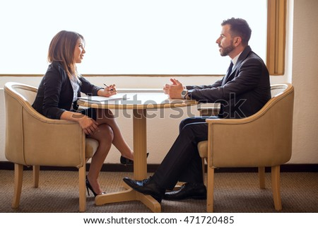 Full length view of a young female recruiter meeting a male candidate for a business position and talking about his resume