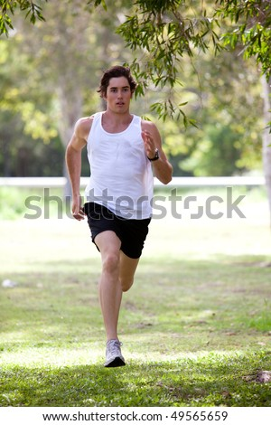 Full length view of a young man jogging in an outdoor setting. He is wearing a tank top and shorts. Vertical shot.