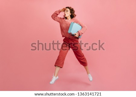 Full length view of brunette woman holding blue valise. Studio shot of caucasian lady with suitcase posing on pink background.