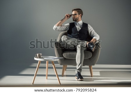 full length view of handsome stylish young man sitting in armchair and looking away