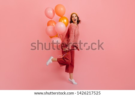 Full length view of joyful lady jumping with air balloons. Studio shot of laughing birthday girl posing on pink background.