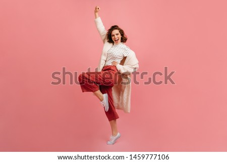 Full length view of pleased young lady in coat. Studio shot of positive girl fooling around on pink background.