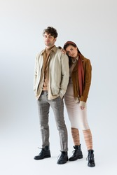 Full length view of stylish woman in autumn outfit leaning on man standing with hands in pockets on grey