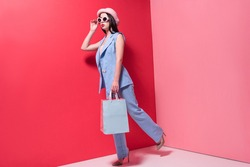 full length view of stylish young woman in hat and sunglasses holding shopping bags and looking away on pink