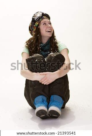 Full length view of teenage girl sitting, hugging knees, dressed in winter clothes. White background