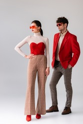 full length view of trendy woman with hand on hip and stylish man with hand in pocket looking away on grey
