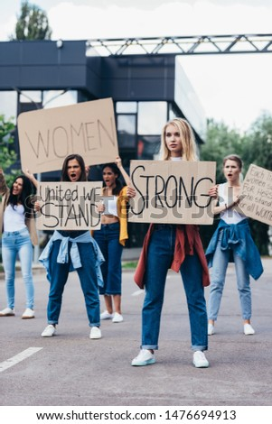 full length view of woman holding placard with word strong near feminists on street #1476694913