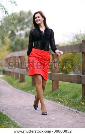 Full length, walking woman  red skirt