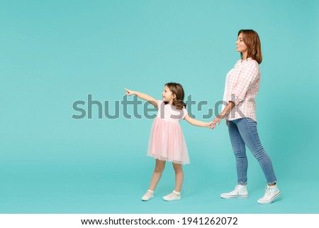Full length woman in pink clothes have fun with child baby girl 5-6 years old. Mommy little kid daughter walk go step isolated on pastel blue azure background studio. Mother's Day love family concept