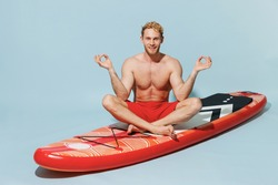 Full length young blond strong man in red shorts swimsuit sit on sup board spread hands in yoga om gesture relax meditate isolated on pastel blue background Summer vacation sea rest sun tan concept