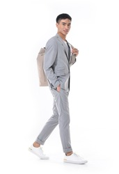 full length young businessman concept, young business consultant standing for camera. Business portrait of young man in gray suit with backpack