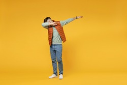 Full length young caucasian fun man in orange vest mint sweatshirt glasses doing dab hip hop dance hands move gesture youth sign hiding cover face isolated on yellow color background studio portrait.