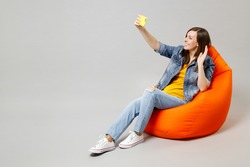 Full length young caucasian woman in casual denim jacket yellow t-shirt sitting in bean bag chair do selfie shot on mobile cell phone waving hand greeting isolated on grey background studio portrait.