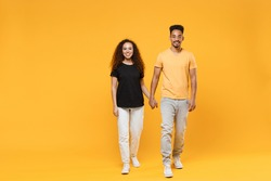 Full length young couple two fun american friends family happy fun smiling african man woman together in yellow black t-shirt hold hands walk go dating isolated on orange background studio portrait
