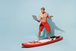 Full length young freelancer man 20s wear red shorts swimsuit stand on sup board point finger on laptop pc computer surfing isolated on pastel blue background Summer vacation sea rest sun tan concept