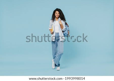 Full length young happy african american girl teen student wear denim clothes backpack hold books isolated on blue color background studio portrait Education in high school university college concept. Foto stock ©