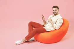 Full length young happy fun man in jacket white t-shirt sitting in bean bag chair using mobile cell phone chat online in social network show thumb up gesture isolated on pastel pink background studio.