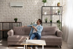 Full length young man wearing glasses holding using air conditioner remote controller, relaxing, sitting on couch, switching, setting comfort temperature in modern living room, enjoy fresh air