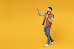 Full length young smiling friendly man in orange vest mint sweatshirt glasses do selfie shot on mobile phone show victory v-sign gesture isolated on yellow background studio. People lifestyle concept