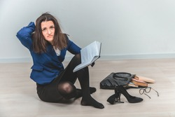Full-length young teacher with tousled hair, sitting on the floor in complete mess around her, keeping hand on the head, looking at the camera with suffering eyes.