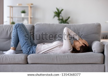 Full length young woman lying on sofa suffers from heartache cover face with hands crying feels desperate unhappy unwell having mental pain or serious health problems, beak up divorce abortion concept
