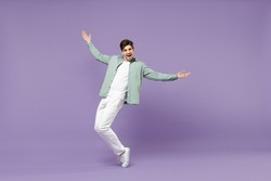Full lengthoverjoyed caucasian man in casual mint shirt white t-shirt standing on toes dancing leaning back fooling around isolated on purple color background studio portrait People lifestyle concept