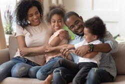 Full mixed-race family sit on couch cuddling laughing feels happy moving at new home, concept of loving parents next generations Z, new mom and dad for adopted kids siblings, protection care and love