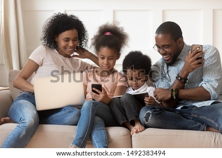 Full mixed-race family sit on couch having bad habit devices overuse addicted with electronic gadget laptop smartphone and tablet users spending lazy weekend at home, dependence of modern tech concept #1492383494