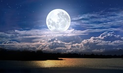 Full moon and cloudy sky over the night lake