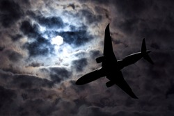 Full moon and silhouette passenger plane on  cloudy sky background. Danger of a airplane crash in bad weather. Dramatic Halloween night. Airliner makes a night flight in stormy weather.