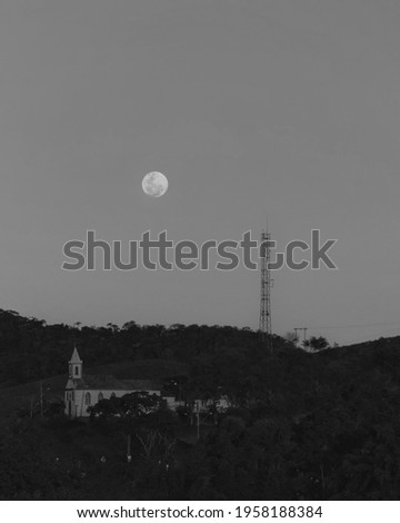Full moon and the church of my village, just behind it, a cemetery. stock photo
