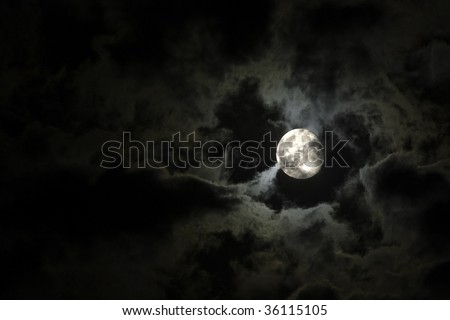 Stock Photo Full moon close-up and eerie white clouds against a black night sky