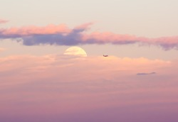 Full moon hiding behind dusky pink and purple clouds at sunset with tiny plane passing by.