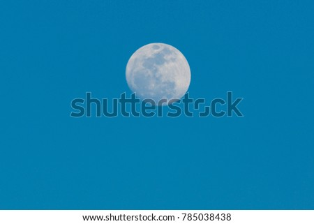 full moon on blue sky background in the daytime #785038438