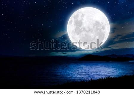 Full moon on night lake background.