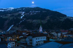Full moon over a small alpine town. Ski resort Zell am Ziller, Tyrol, Austria. Early March.