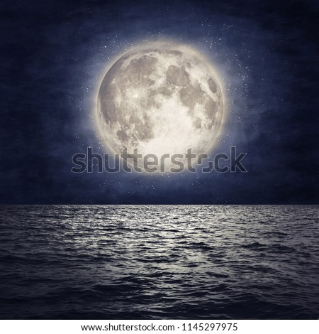Full moon over sea surface with reflection