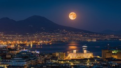 Full moon rises above Mount Vesuvius, Naples and Bay of Naples, Italy. Moonlight reflected in calm sea. Elements of this image furnished by NASA.