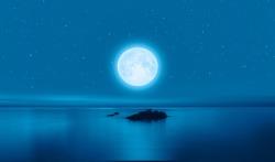 Full moon rising above calm sea