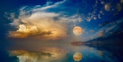 Full moon rising above serene sea in sunset sky. Elements of this image furnished by NASA
