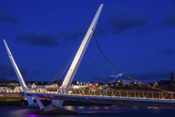 Full moon rising by Peace Bridge in Derry. Derry, Northern Ireland, United Kingdom.