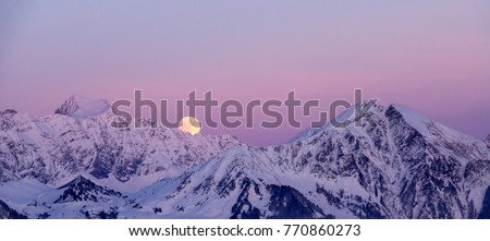 full moon rising over a winter mountain landscape near Klosters in the Swiss Alps