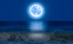 Full moon rising over empty ocean at night with Power waves crashing over rocks from the ocean