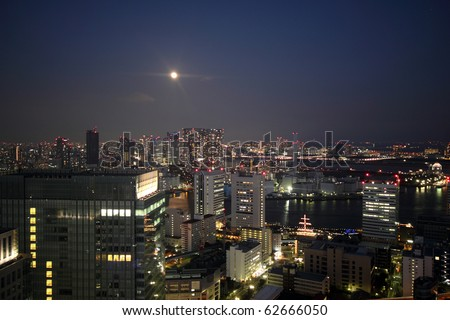 Full moon rising over night skyline of Tokyo, Japan with illuminated buildings and waterways