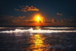 Full moon rising over sea waves. Dramatic sunset over beach.