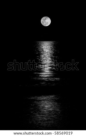 Full moon setting on the horizon in the ocean with reflection shining through. Black and White.
