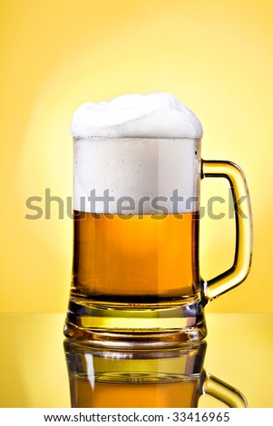 Full mug of lager beer on yellow