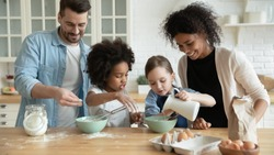 Full multi ethnic family with adorable daughters gathered in modern kitchen cooking pancakes together. Cake mix preparation, make yummy home-made dessert, enjoy communication and cookery hobby concept