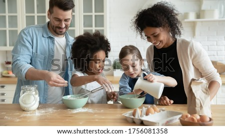 Full multi ethnic family with adorable daughters gathered in modern kitchen cooking pancakes together. Cake mix preparation, make yummy home-made dessert, enjoy communication and cookery hobby concept Foto d'archivio ©